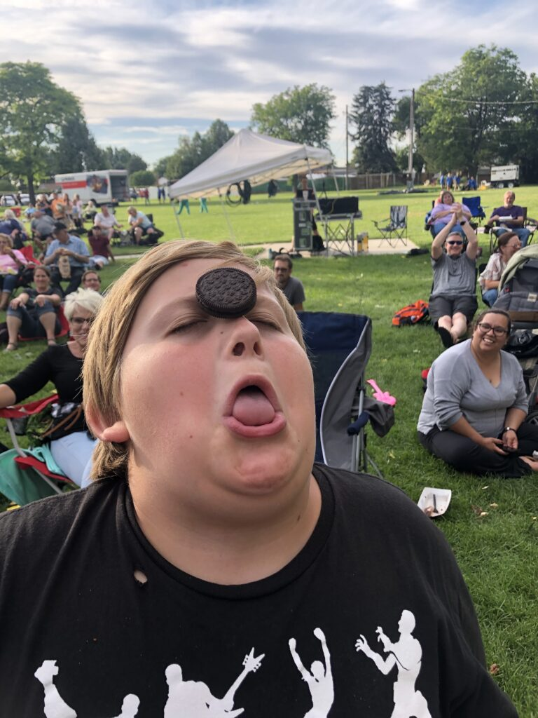 boy with cookie on nose and mouth open