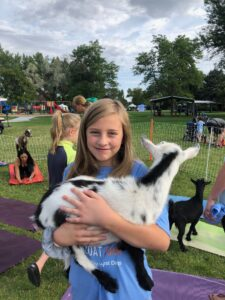Young girl holding baby goat